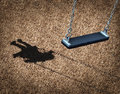 Missing child concept with an empty playground swing and the shadow of a little girl on the park floor as a symbol of children Stock Images