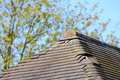 Missing damaged roof tiles worn ridge with copyspace Stock Image