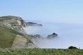 Mist on coast near lulworth cove dorset morning sea Stock Photos