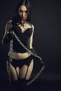 Mistress in black seductive girl lingerie with chains over dark background Royalty Free Stock Images