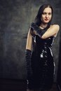 Mistress in black seductive gothic girl latex dress over grunge background Royalty Free Stock Photo