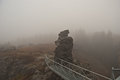 Misty autumn day on vysoky kamen hill in krusne hory mountains czech german borders with few rocks and bridge with guard rail Royalty Free Stock Photo
