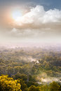 Misty forest hill with sun and clouds Royalty Free Stock Photo