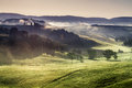 Misty hills and meadows in tuscany at sunrise italy Royalty Free Stock Images