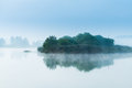 Misty lake morning island tranquil blue by the near forest Royalty Free Stock Images