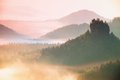 Misty landscape with fog between hills and orange sky within sunrise Royalty Free Stock Photo