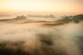Misty melancholic morning. View into long deep valley full of fresh  spring mist. Landscape within daybreak after rainy night Royalty Free Stock Photo