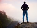 Misty morning. Hiker is standing on the peak of rock in rock empires park and watch over misty and foggy morning valley Royalty Free Stock Photo
