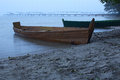 Misty morning on the lake. Two boats at the shore near old abandoned pier Royalty Free Stock Photo