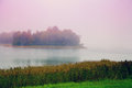 Misty morning mist over lake the with an island at Royalty Free Stock Photo