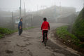 Misty morning a young boy is riding bicycle in the at lava village near darjeeling lava is a tourist destination popular for its Stock Photography