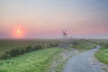 Misty summer sunrise over dutch farmland with windmill holland Stock Photo