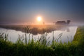 Misty sunrise over river in farmland groningen netherlands Stock Photos