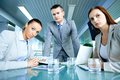Misunderstanding serious boss with his two employees looking at camera with displeasure Royalty Free Stock Image