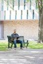 Mittlerer erwachsener student sitting on bench am campus Lizenzfreie Stockfotos