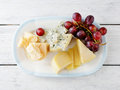 Mix cheeses with grapes on plate Royalty Free Stock Photo