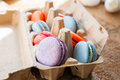 Mix of colorful macarons in a craft paper egg container