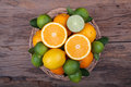 Mix of fresh citrus fruits in basket on wood Royalty Free Stock Photo