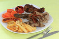 Mix grill steak include drumstick bacon pork beef sausage and vegetable with french fries Stock Images