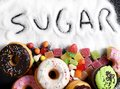 Mix of sweet cakes, donuts and candy with sugar spread and written text in unhealthy nutrition Royalty Free Stock Photo