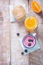 A mix of three smoothies with blueberry, orange and peach on a wooden background with copy space Royalty Free Stock Photo