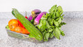 Mix tropical vegetables iv in a container on a kitchen granite surface counter Stock Photo