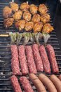 Mixed assortment of marinated meat, chicken, and prawns grilling on hot coals on a BBQ Royalty Free Stock Photo