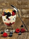 Mixed berry granola and yogurt parfait on wood healthy background with spoon Stock Photography
