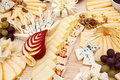 Mixed cheeses on light wooden board Royalty Free Stock Images