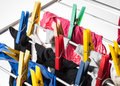 Mixed clean laundry pinned with colourful clothespins on white background Royalty Free Stock Image