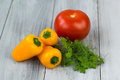 Mixed fresh colored vegetables, mini paprika, tomato and fresh herbs on a wooden background Royalty Free Stock Photo