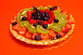 Mixed fruit tart on a festive red background Royalty Free Stock Image