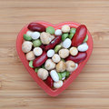 Mixed legume beans in a heart bowl close up Stock Photos