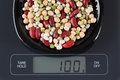 Mixed legume beans on kitchen scale in a black plate digital displaying gram Stock Images