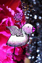 Mixed media bird art illustration and photography white and pink purple holds a flower in a garden of silver bokeh and bright Stock Photos