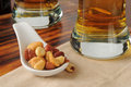 Mixed nuts and beer a sample spoon of bar snacks with tall glasses of in the background Royalty Free Stock Image