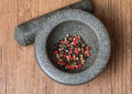 Mixed pepper in mortar on wooden background Royalty Free Stock Photo