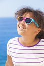 Mixed race african american girl child sunshine sunglasses a beautiful and happy female wearing in bright on vacation in front of Stock Photography