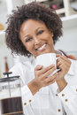 Mixed race african american girl drinking coffee a beautiful happy or young woman cafetiere in her kitchen at home Stock Photo