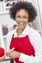 Mixed race african american woman cooking kitchen a beautiful girl or young looking happy wearing a red apron in her at home Stock Photography
