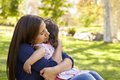 Mixed race Asian mum embracing her young daughter in a park Royalty Free Stock Photo