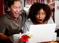 Mixed race couple in coffee house with laptop comp Stock Photos