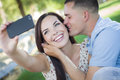 Mixed race couple taking self portrait in park happy with a smart phone the Royalty Free Stock Image