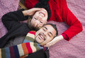 Mixed race couple wearing winter clothing on picnic blanket in a park young Stock Image