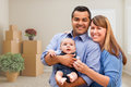 Mixed Race Family with Baby in Room with Packed Moving Boxes Royalty Free Stock Photo
