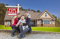 Mixed race family home for sale real estate sign happy in front of their new and a Stock Image