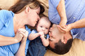 Mixed Race Family Kissing Baby on a Blanket Royalty Free Stock Photos