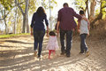 Mixed race family walking on rural path, close up back view Royalty Free Stock Photo