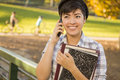 Mixed Race Female Student Holding Books and Talking on Phone Stock Photos
