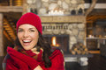 Mixed race girl enjoying warm fireplace in rustic cabin smiling comfortable looking at camera Stock Image
